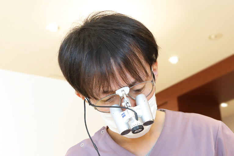 拡大鏡を用いて精密な治療を行っています